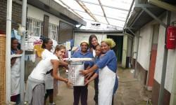 5 Cocineras recibiendo un regalo de las voluntarias